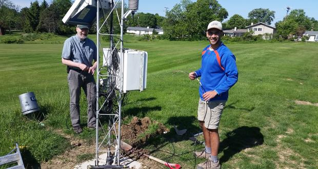 Assistant State Climatologist Jim DeGrand and Undergraduate Research Stephen Maldonado standing near the OARDC-Columbus meteorological tower preparing  to intall soil moisture probes in the ground.